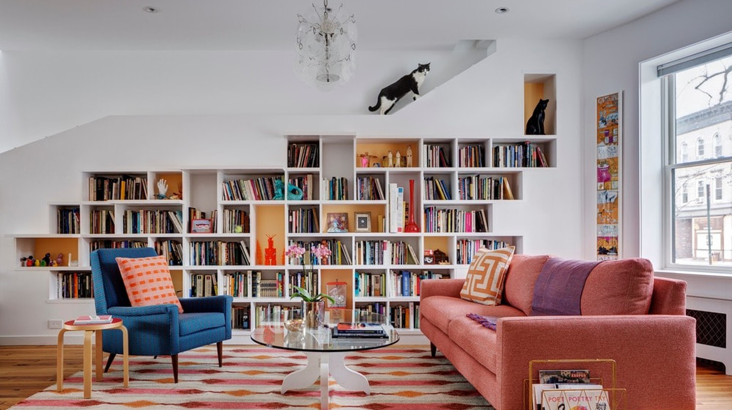 The bookshelf has a platform above it from where the cats can view the daily goings-on