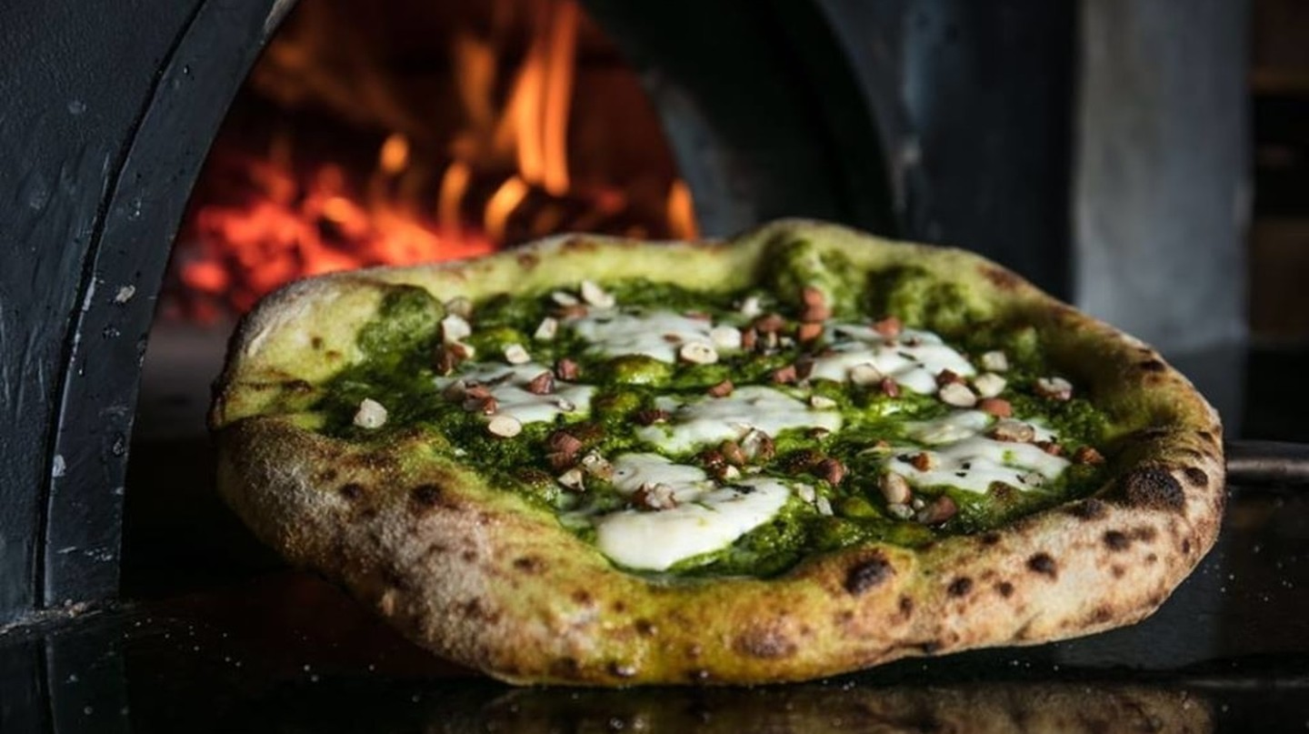 Pizza topped with pesto and freshly chopped nuts