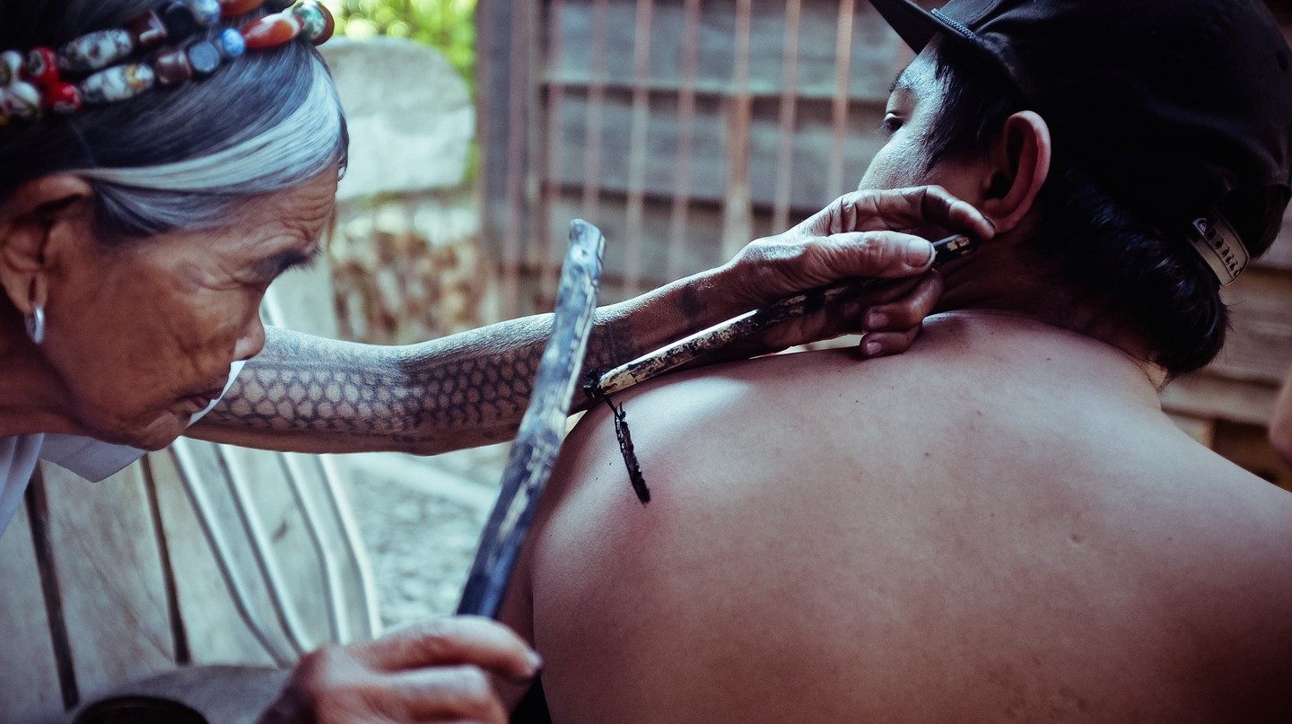 Man getting tattooed by Whang Od