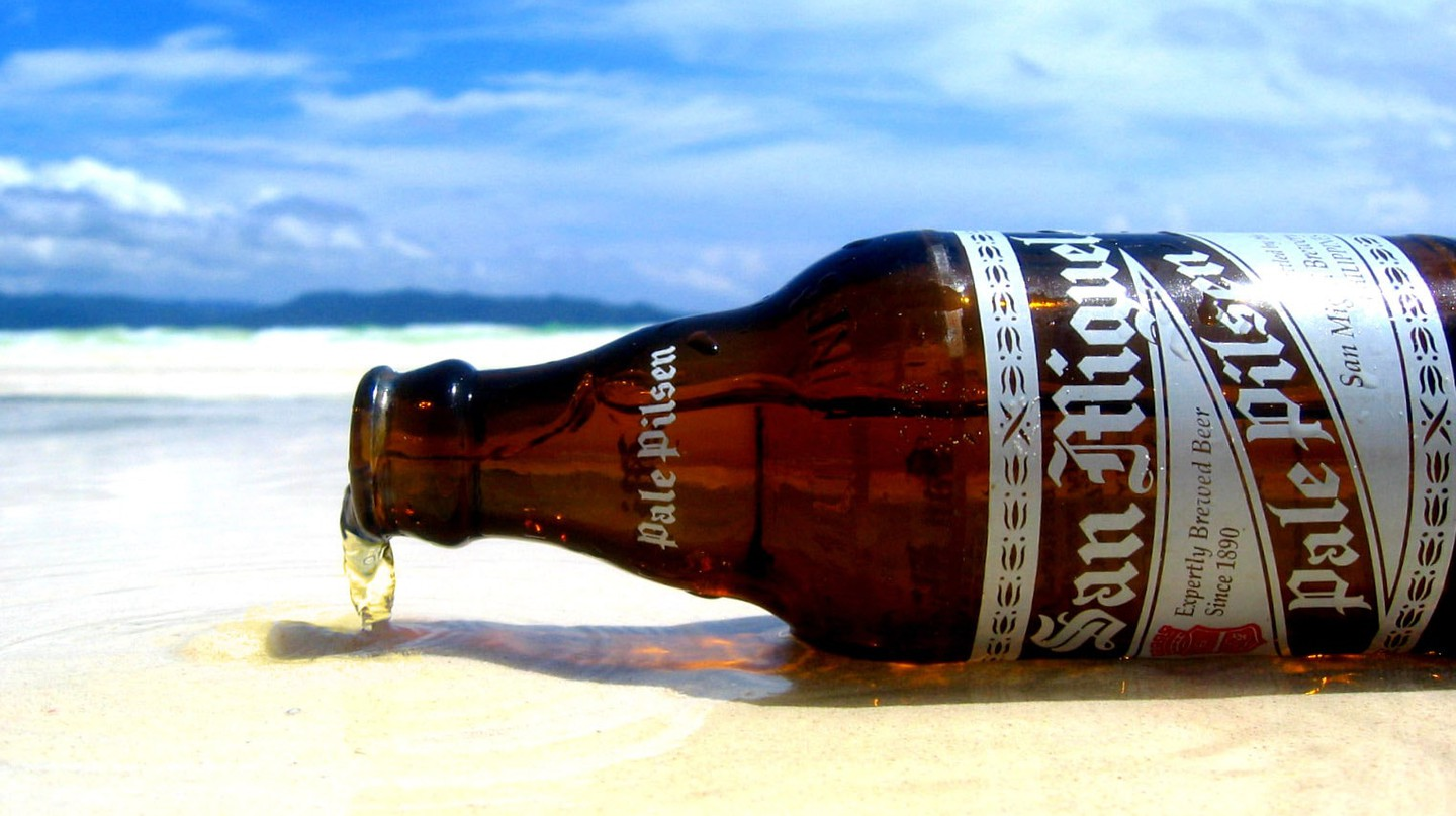 Bottle of San Miguel Pale Pilsen on the beach