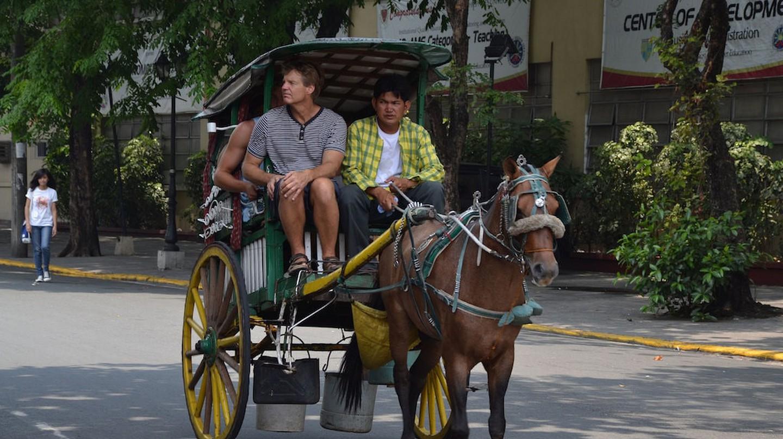 Traveler riding on a local horse cart called a calesa | © Shankar S./Flickr