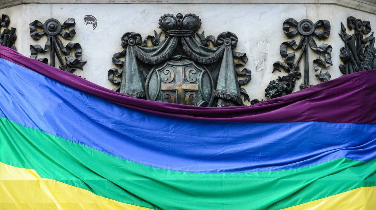 The Pride flag stands in front of the Serbian coat of arms