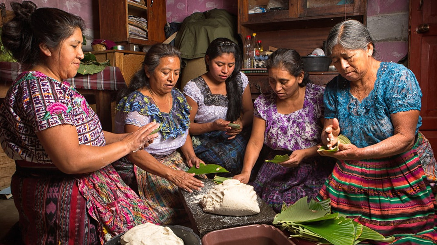 Tzutujil mayan women preparing traditional food together, Guatemala | © Barna Tanko/Shutterstock