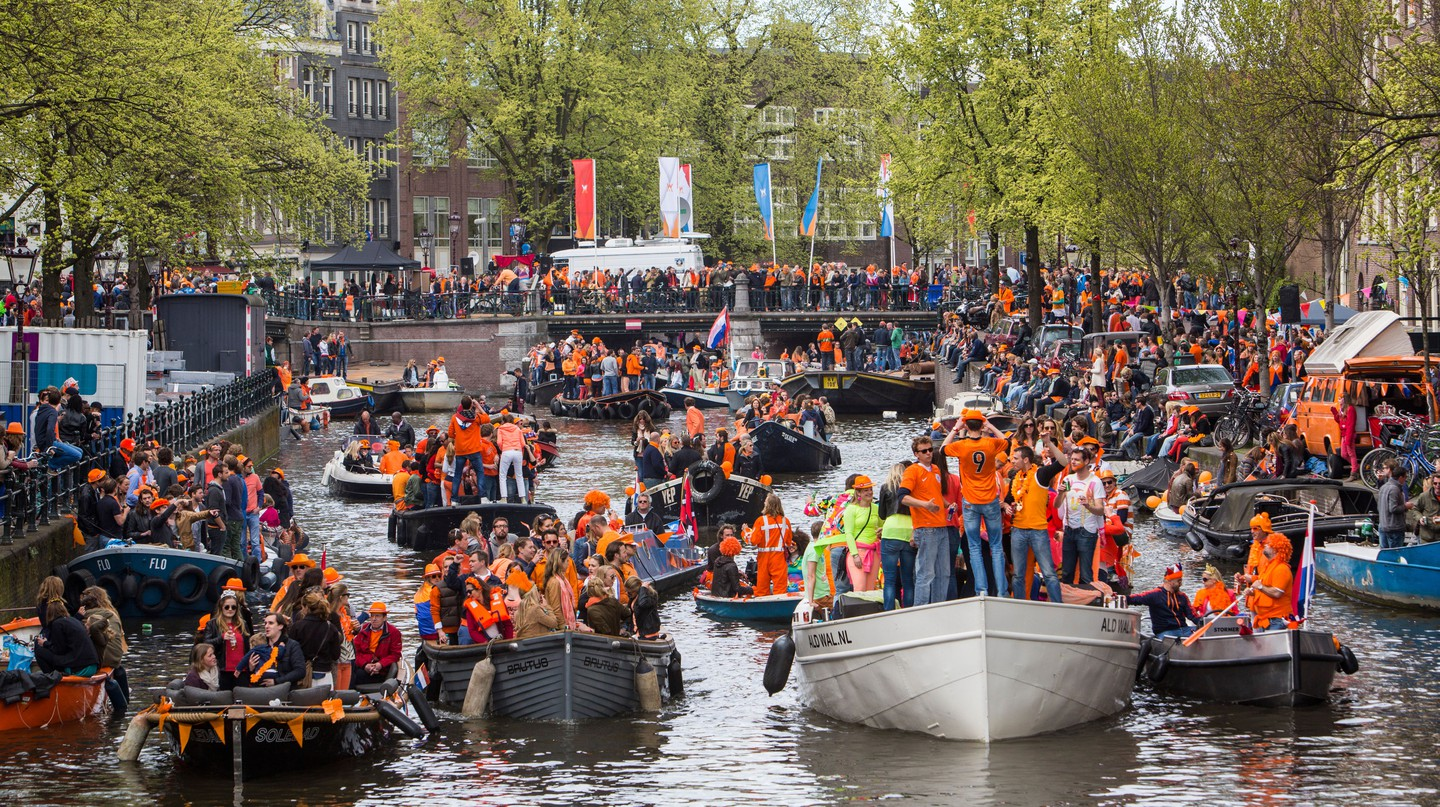 Boat parade in the canals of Amsterdam for annual King's Day, The Netherlands