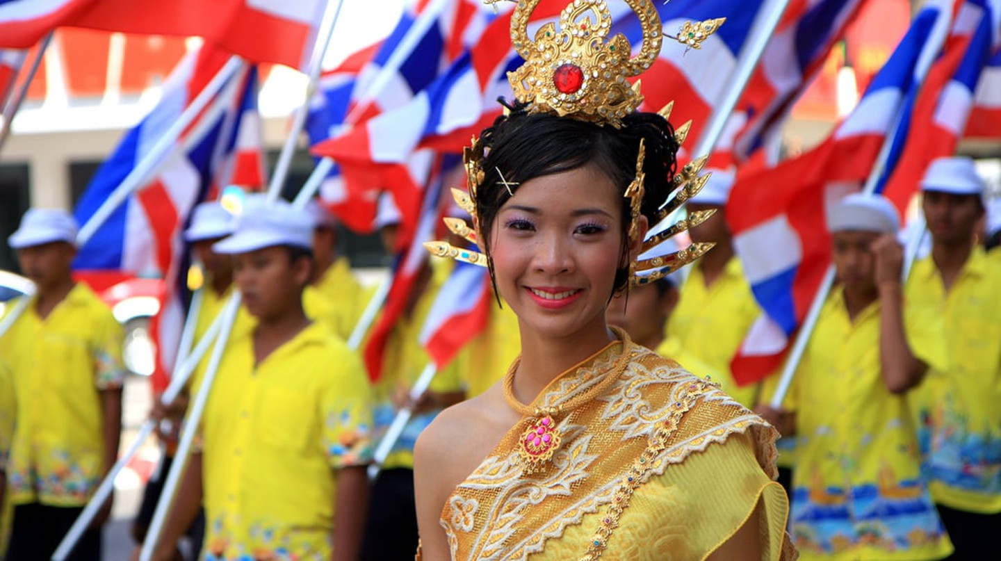 Lady in traditional Thai dress with Thai flags behind her | © Binder.donedat / Flickr