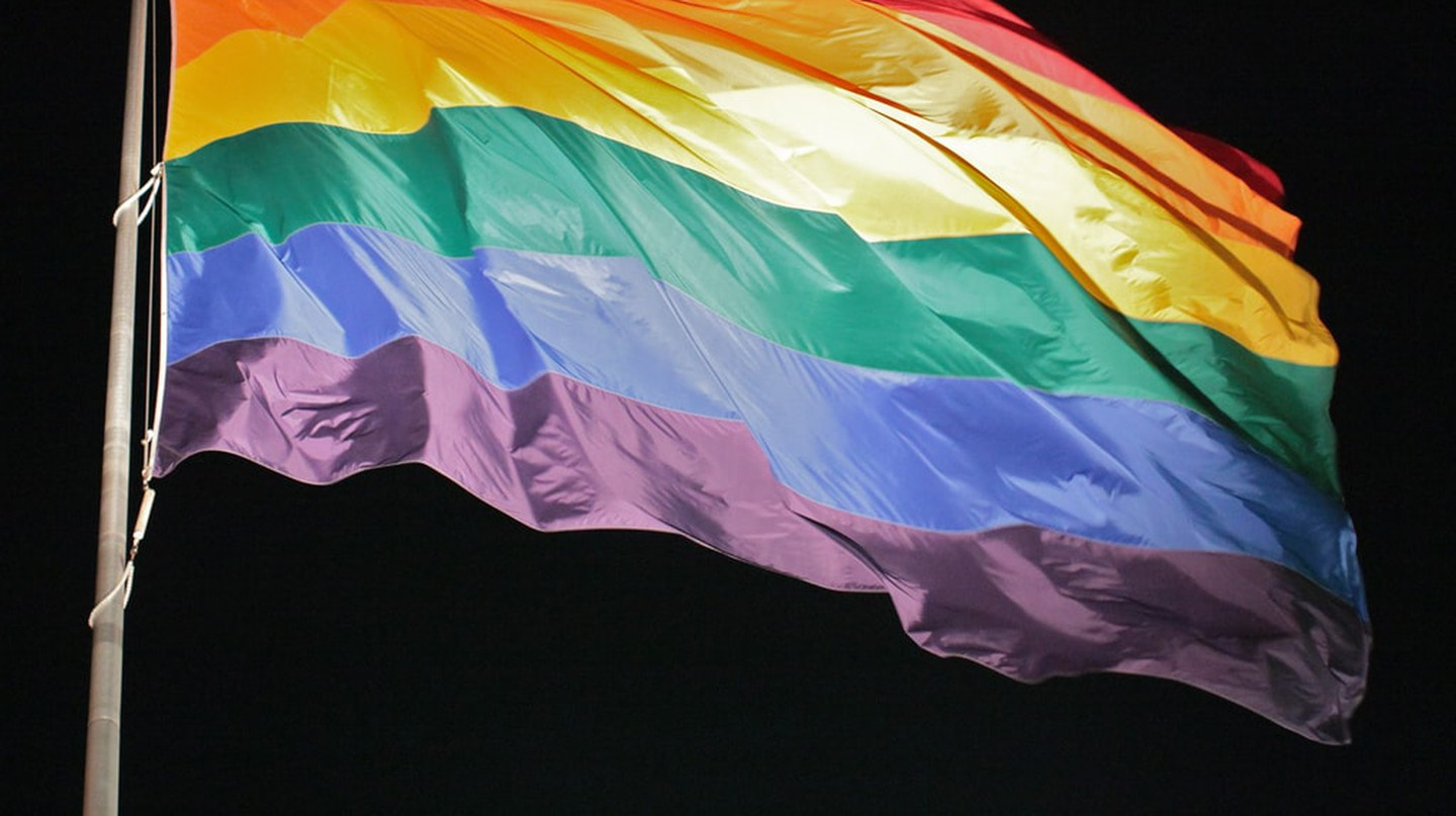 A rainbow Pride flag set against a night sky