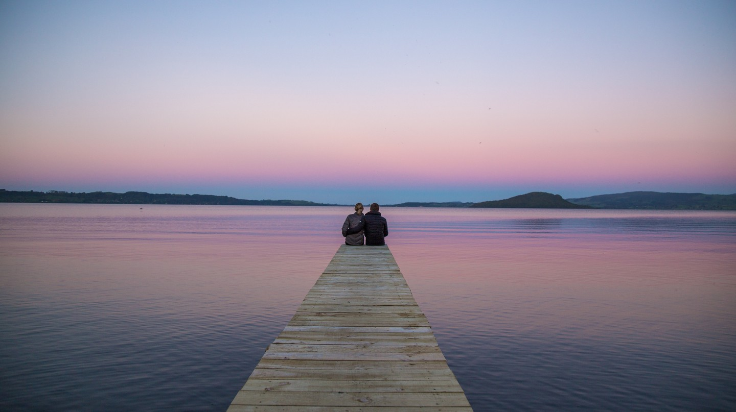 A couple watches the sunset at Lake Rotorua