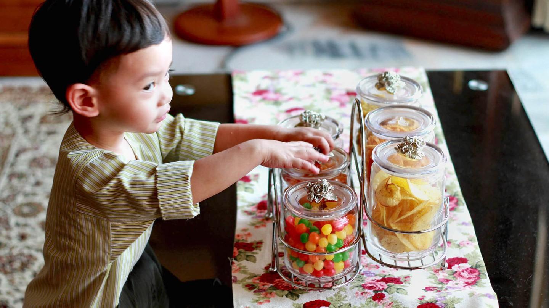 Young child taking Hari Raya snacks from jar