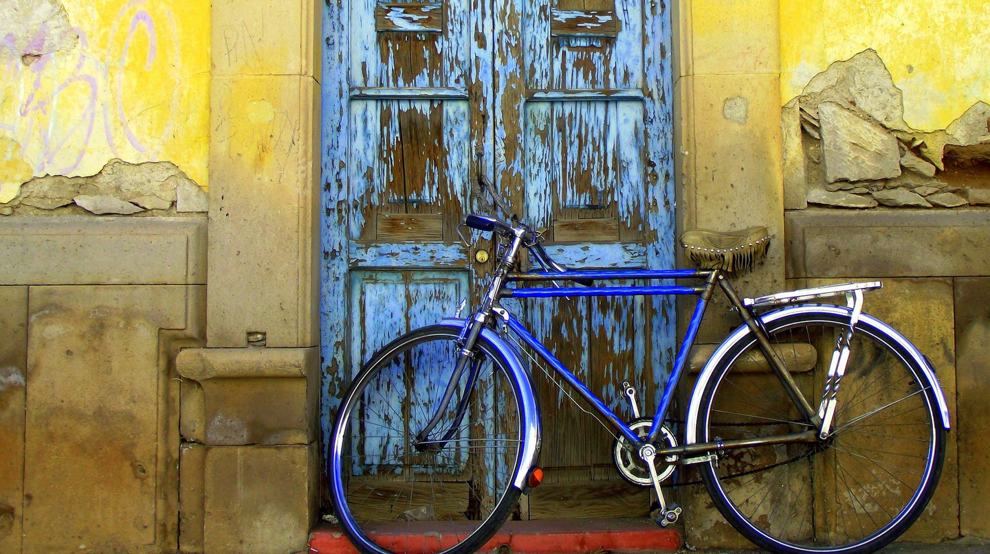 A bike propped against an old doorway in Durango