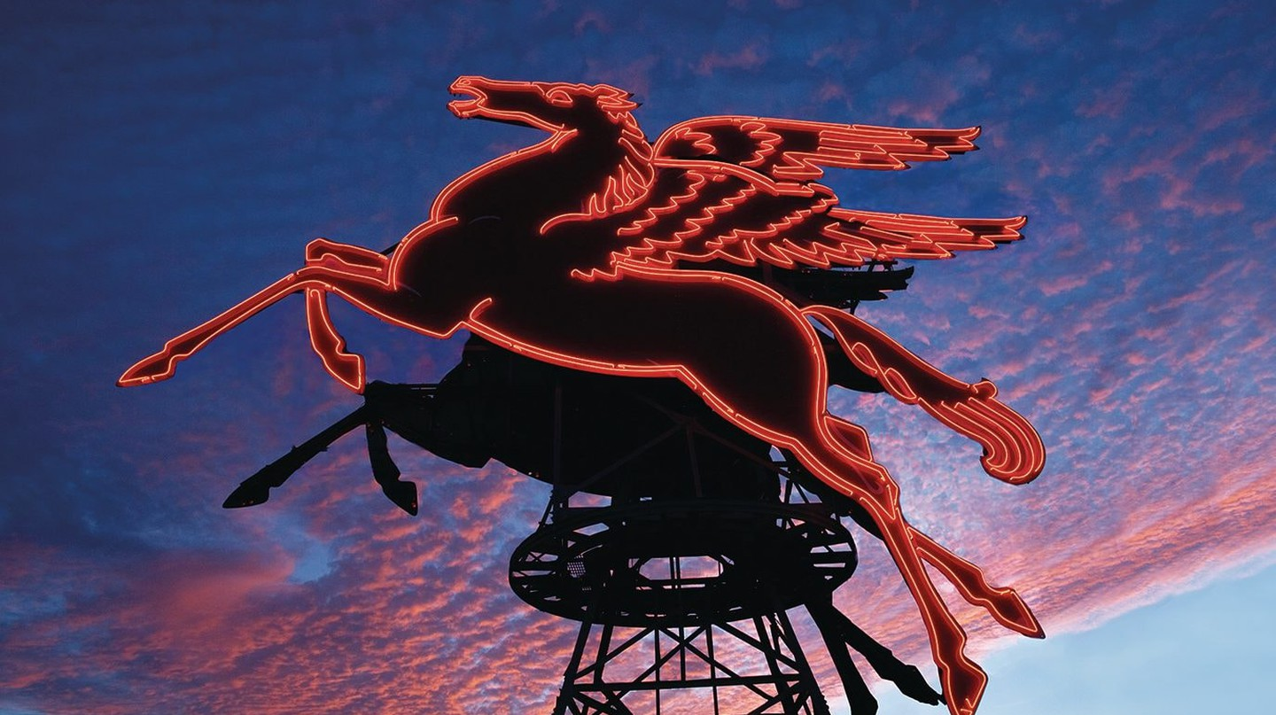 The neon red Pegasus shines bright in front of the Omni Dallas Hotel