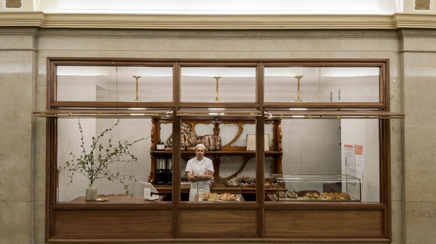 Roger Gural, founder and baker, stands among his many breads and pastries at Arcade Bakery