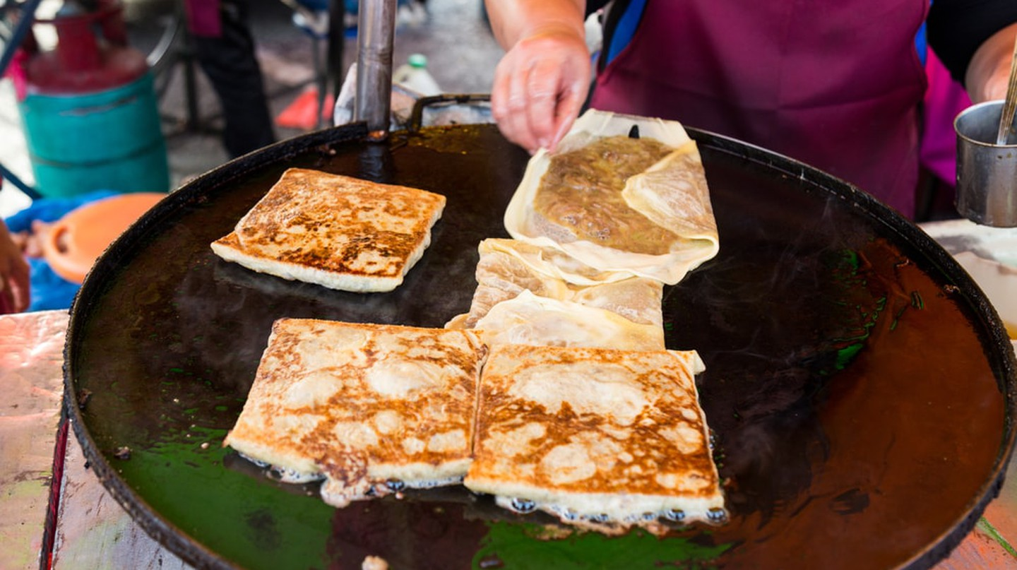 Vendor preparing traditional murtabak cuisine at street bazaar in Malaysia