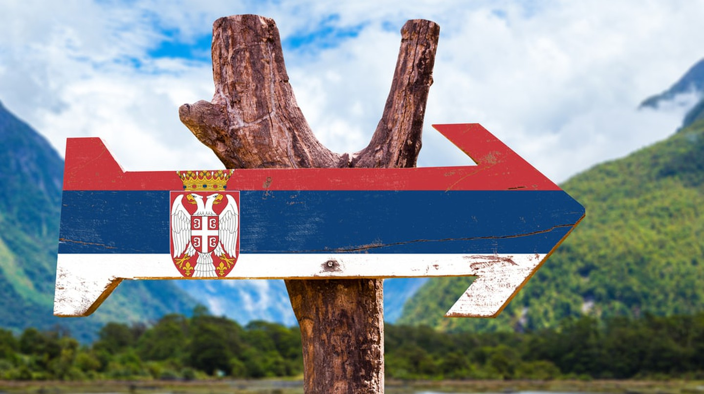 Serbia's flag on a wooden sign with mountains in the background