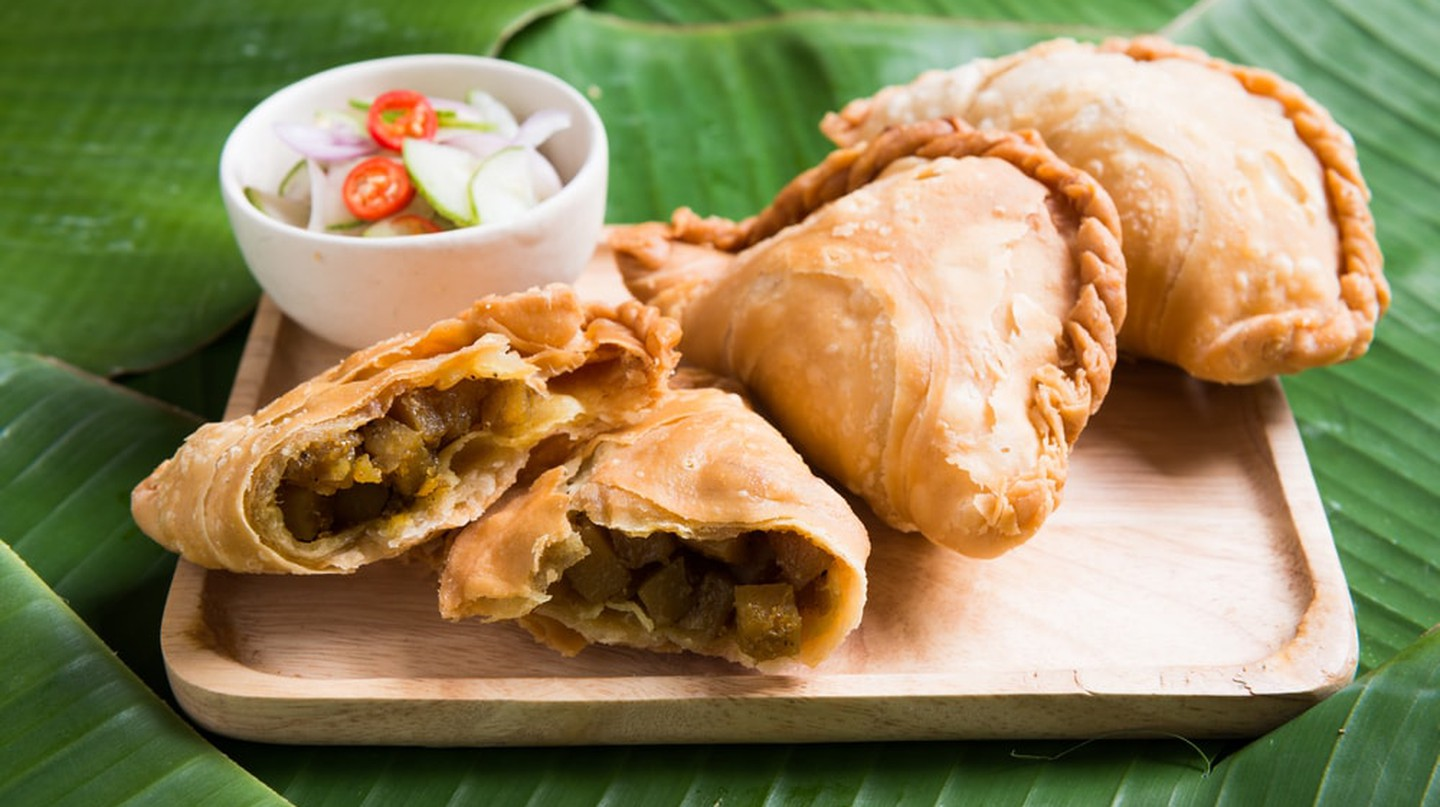 Curry Puff Stuffed Chicken on Banana Leaf Background