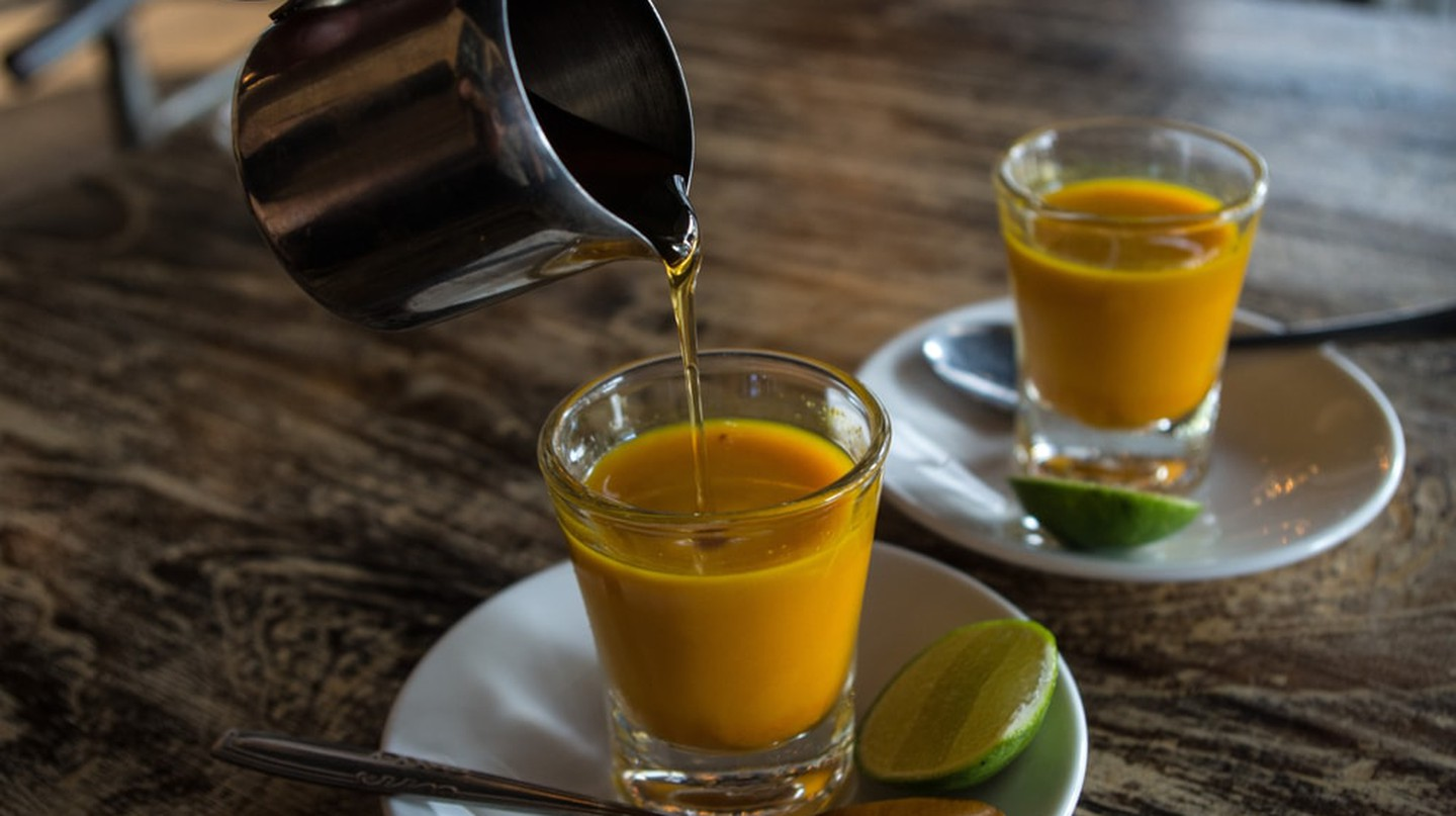 Adding honey to two healthy jamu shots in close-up