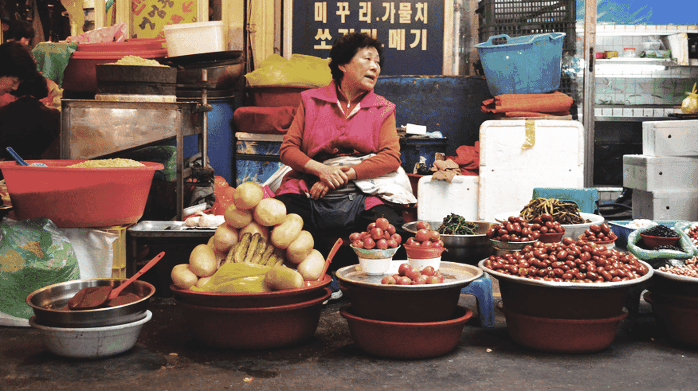 A Korean ajumma selling her wares in a traditional South Korean market