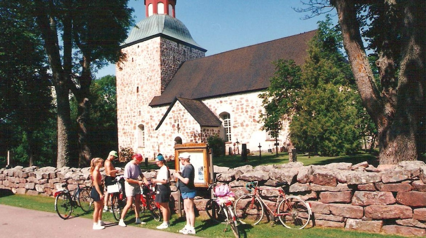 Cyclists stop at Saltvik Church on the Finland Archipelago