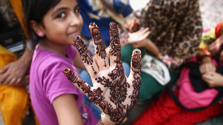 A Pakistani girl shows the henna tattoo on her hand, ahead of Eid al-Fitr