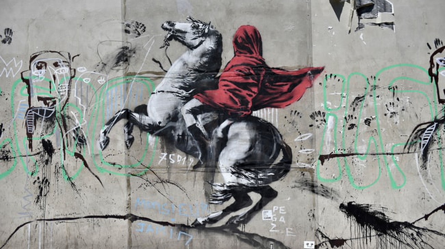 People walk by a recent artwork believed to be attributed to Banksy showing Napoleon rearing his horse, wrapped in a red cloak in the 19th district of Paris, France, June 26, 2018. Several artworks attributed to the anonymous British street artist appeared in the French capital over the last few days. Banksy street art in Paris, France - June 26, 2018