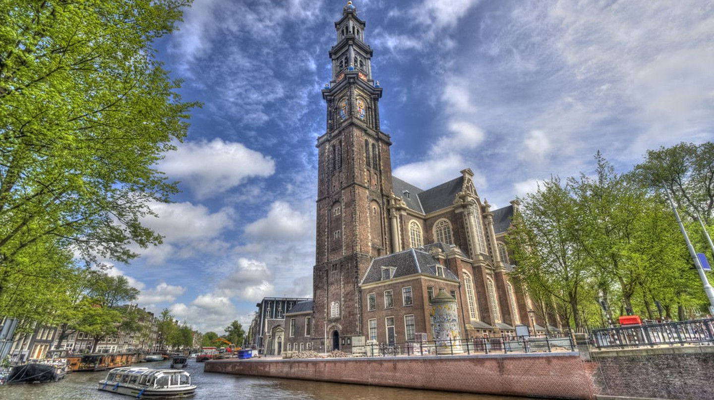 The Westerkerk Church and a tour boat in Amsterdam