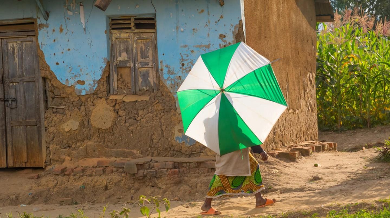 Villager with an umbrella, near Mweya, Uganda