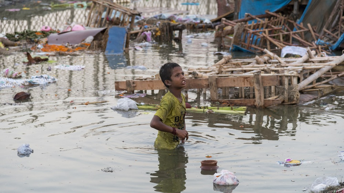 A young boy wading through heavily polluted river waters during the festival of Durga Puja