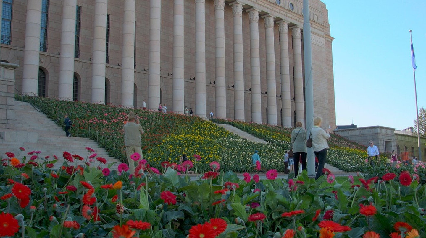 The steps of the Finnish Parliament House decorated with flowers.