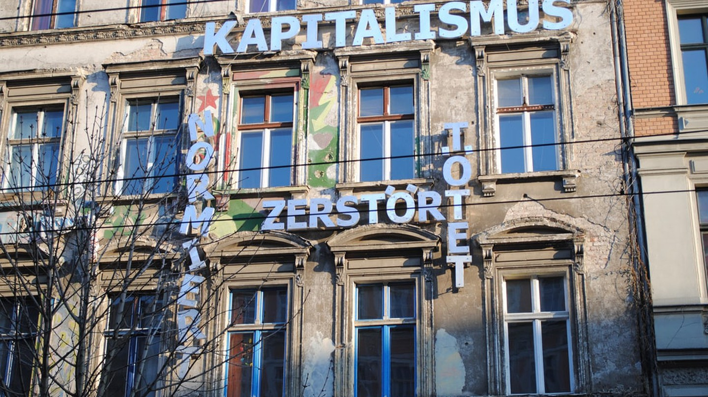 "A former squat in Berlin with the sign ""Capitalism destroys and kills"""