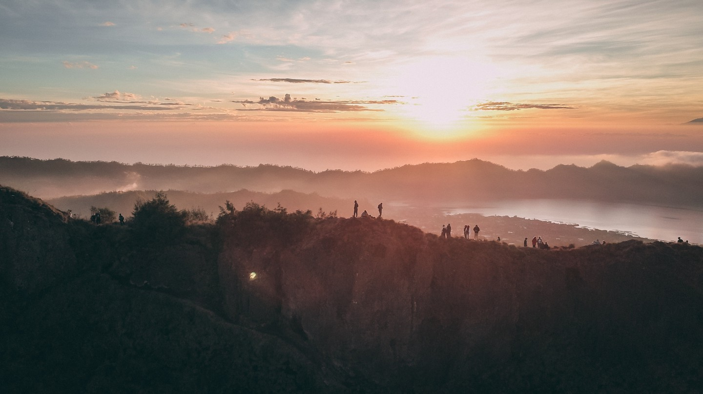 Hikers on Mount Batur caldera at sunrise