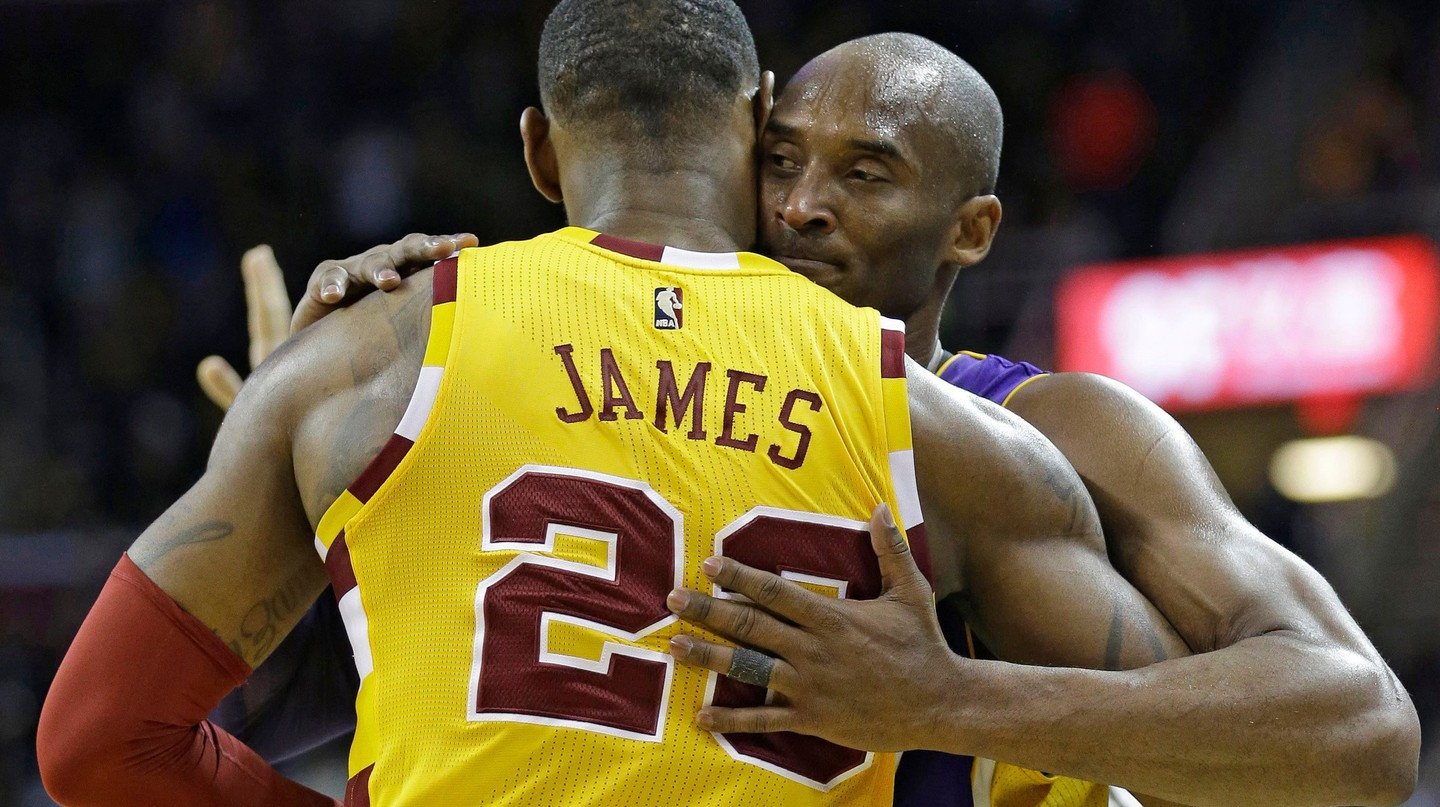 Los Angeles Lakers' Kobe Bryant, back, hugs Cleveland Cavaliers' LeBron James as Bryant leaves the game in the second half of an NBA basketball game, in Cleveland