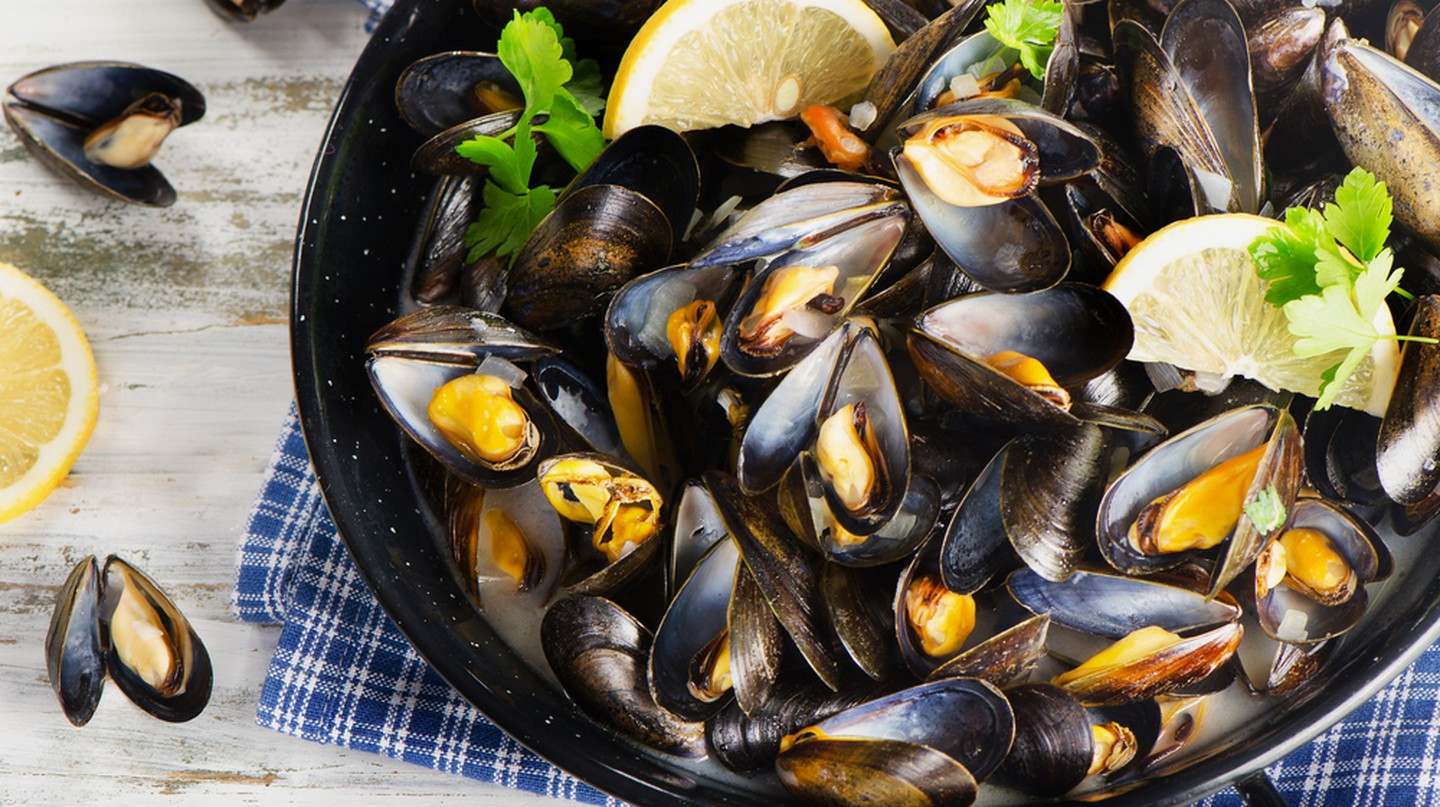 Gourmet mussels served on a napkin garnished with lemon slices