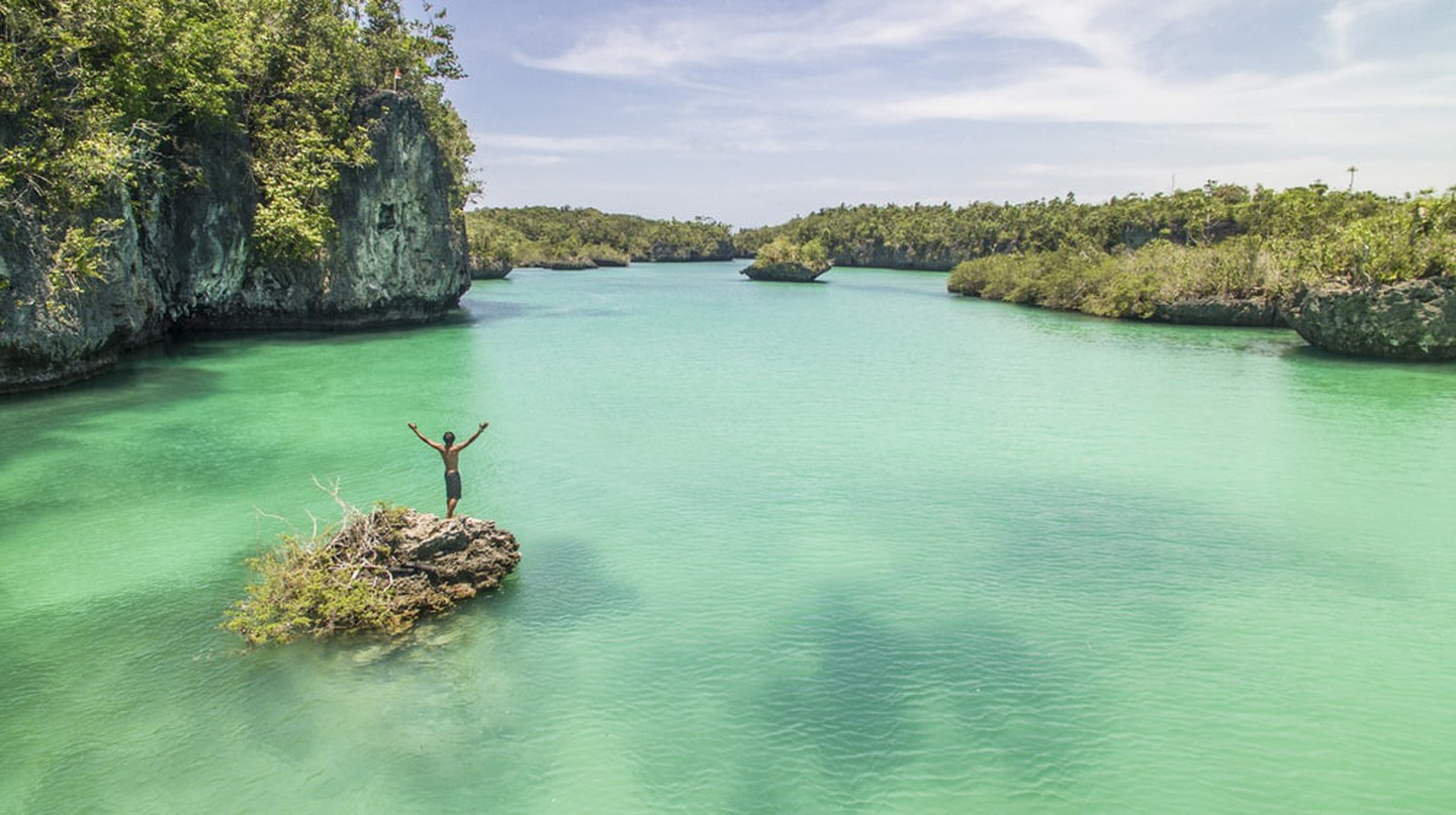 A man standing on a rock in the ocean surrounded by turquoise water in Kai Islands