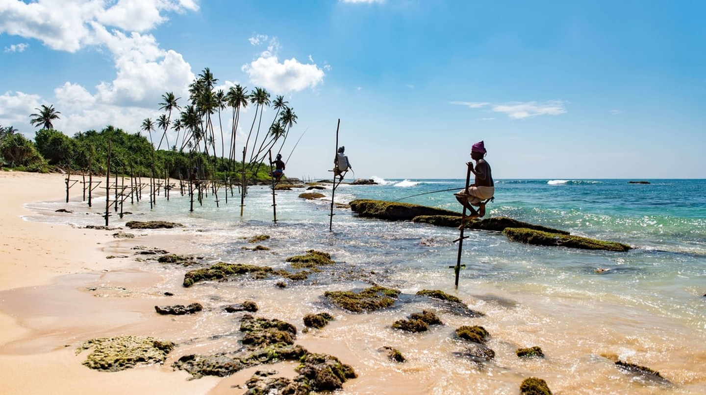 Stilt fishermen by a sun-kissed beach in Sri Lanka awaiting a swarm of fish to pass by the shallow waters