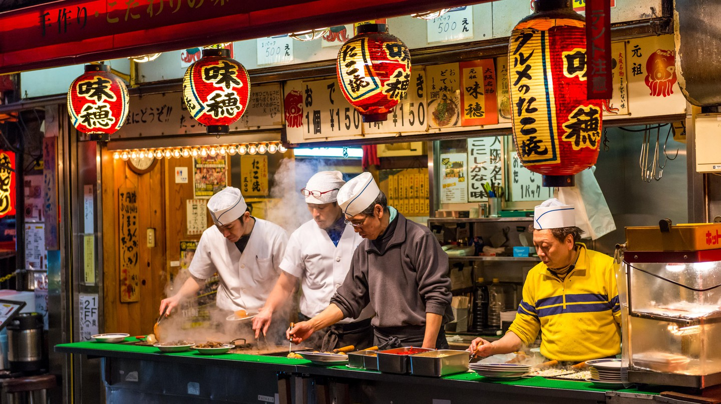 Japanese chefs prepare snack foods at a stall in Osaka, Japan.