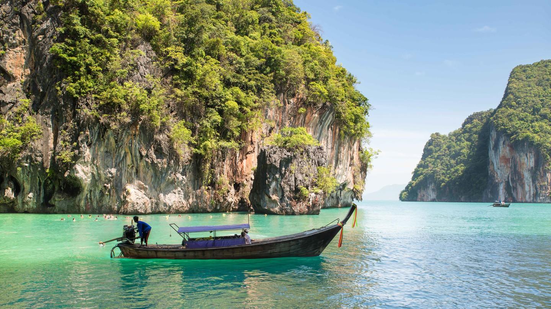 Rocks mountain and longtail boat at Phuket, Thailand.