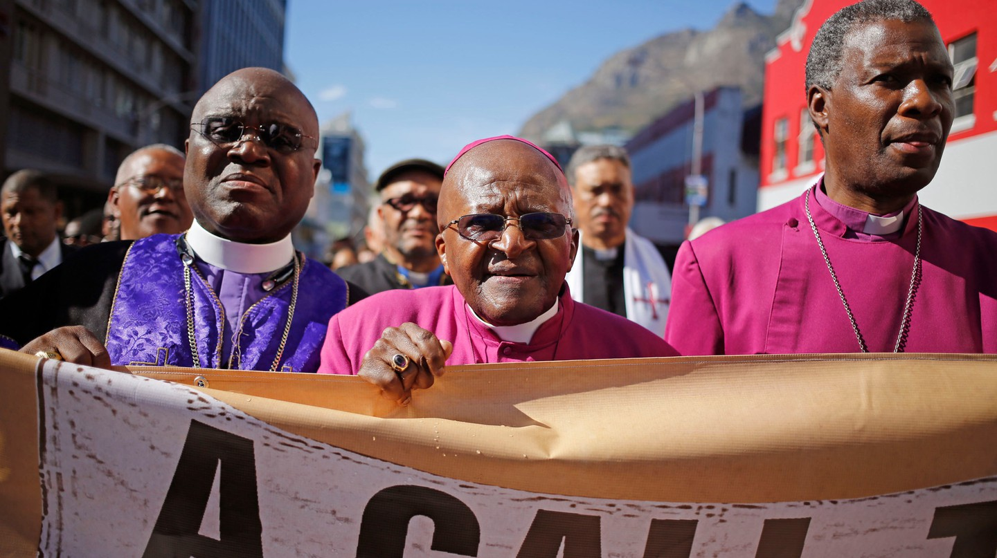 Archbishop Desmond Tutu marches during a rally