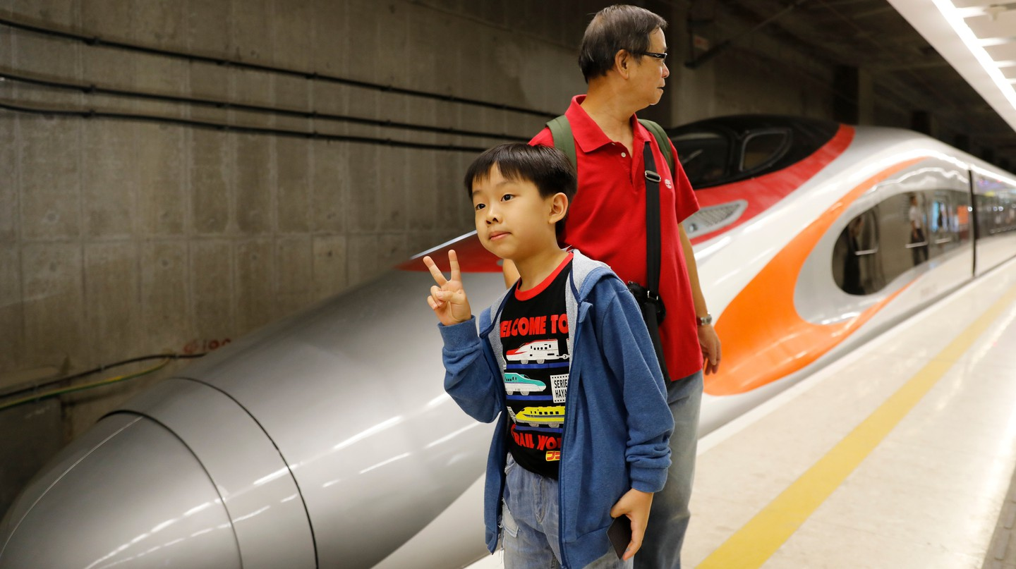 A boy poses with an Express Rail train at the West Kowloon Terminus
