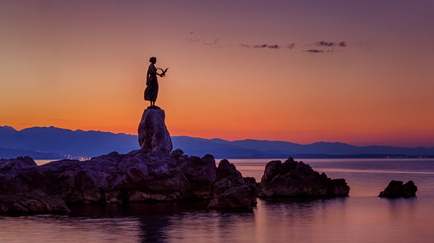 Statue of a girl holding a seagull in Opatija, Croatia.