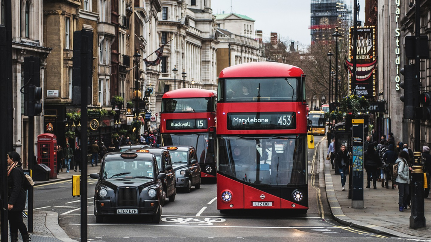A London black cab and a red bus waiting at traffic lights in Trafalgar Square, London.