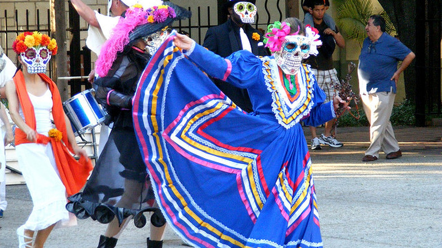 A woman dances during the La Villita parade dressed as a calavera catrina