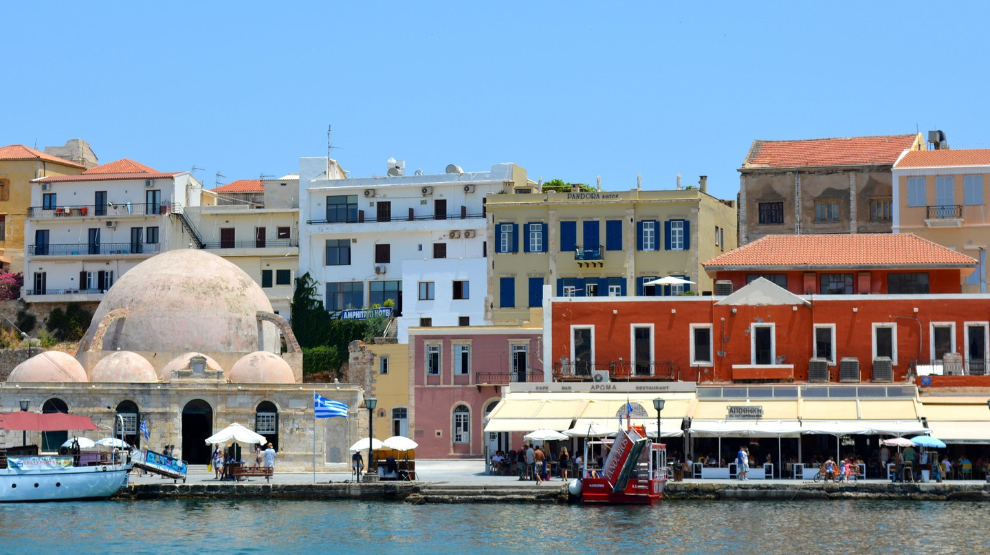 Pastel-colored houses on the seafront in the harbor of Chania, Crete, Greece