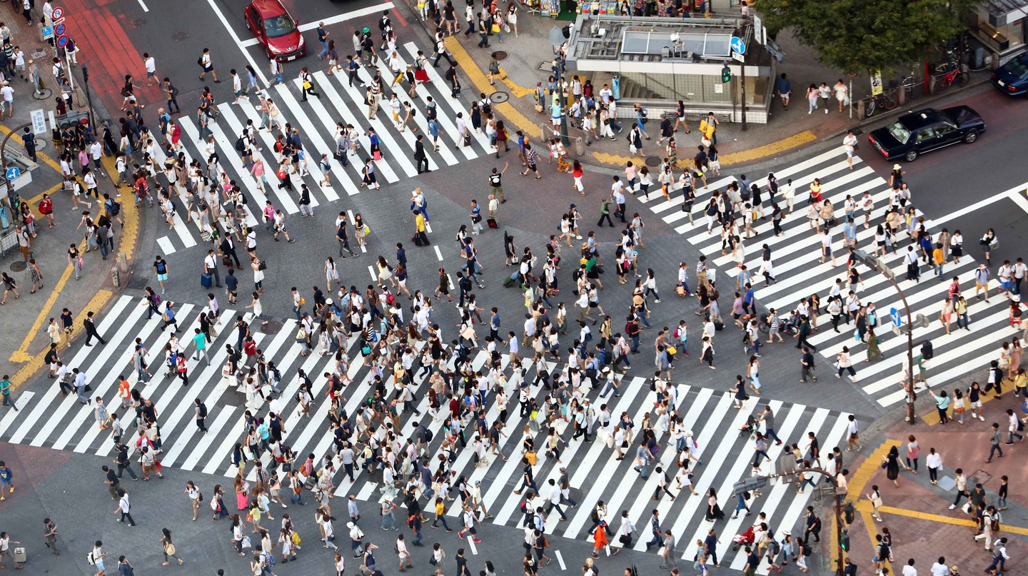 People cross the iconic intersection in Shibuya, Tokyo