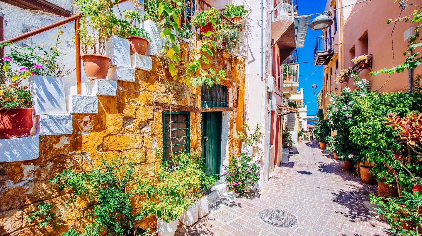 Mediterranean street with stairs and flower pots, Chania, island of Crete, Greece.