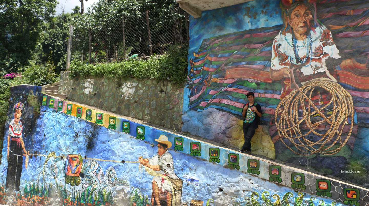 Miguel Ujpán in front of his mural in San Pablo la Laguna, Guatemala |