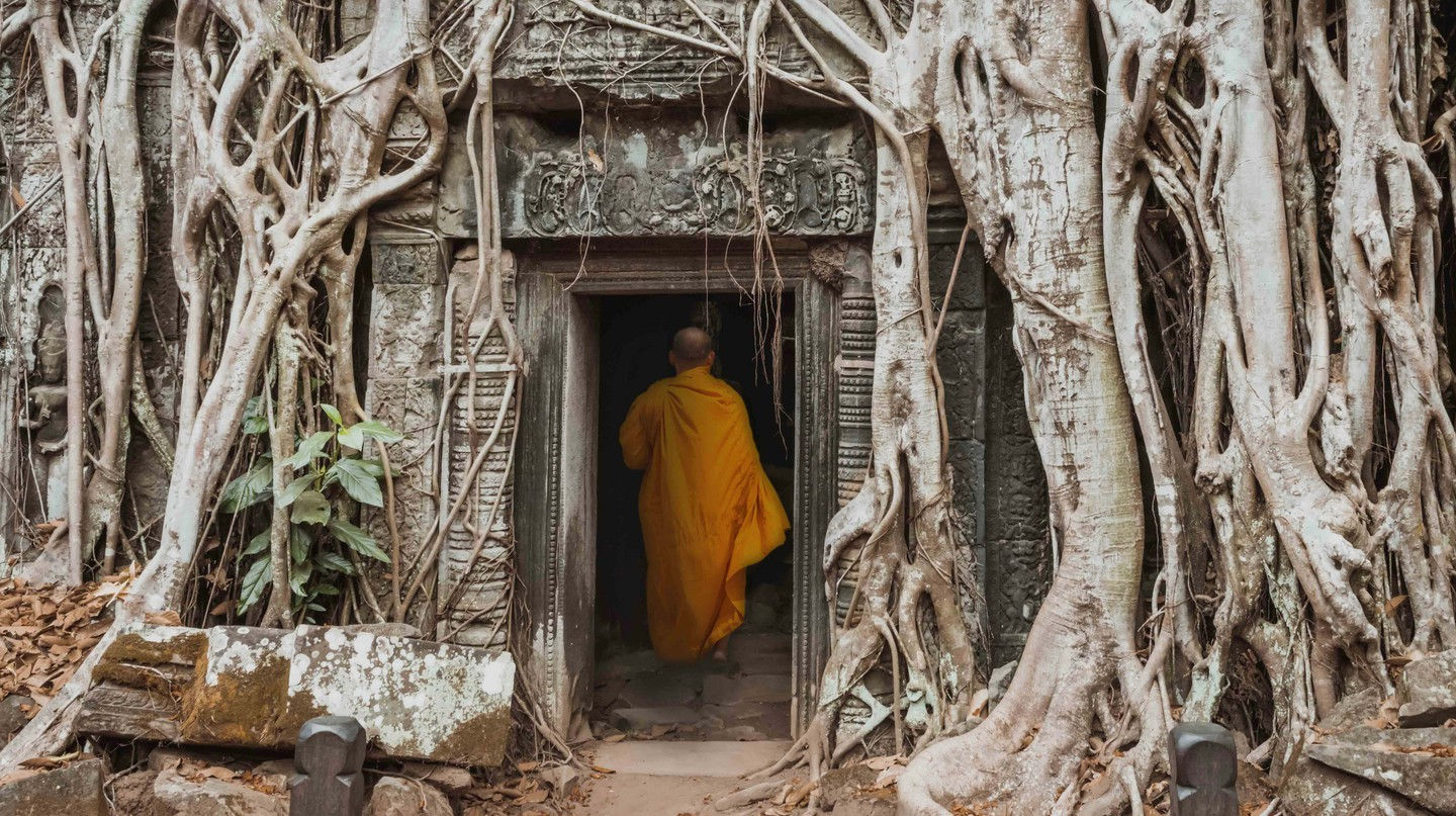 Monk in temple Ta Prom Angkor wat Cambodia landmark.