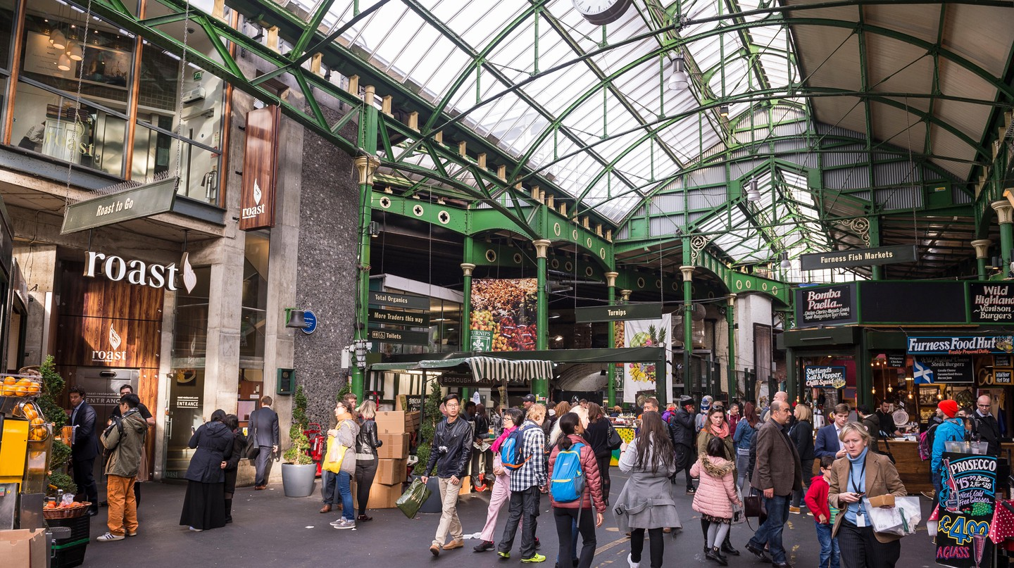 Visitors browse the specialty food stalls at Borough Market, one of London's largest and oldest markets