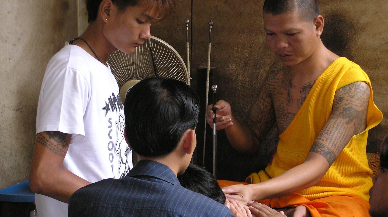 A monk administers a sak yant tattoo at Wat Bang Phra temple