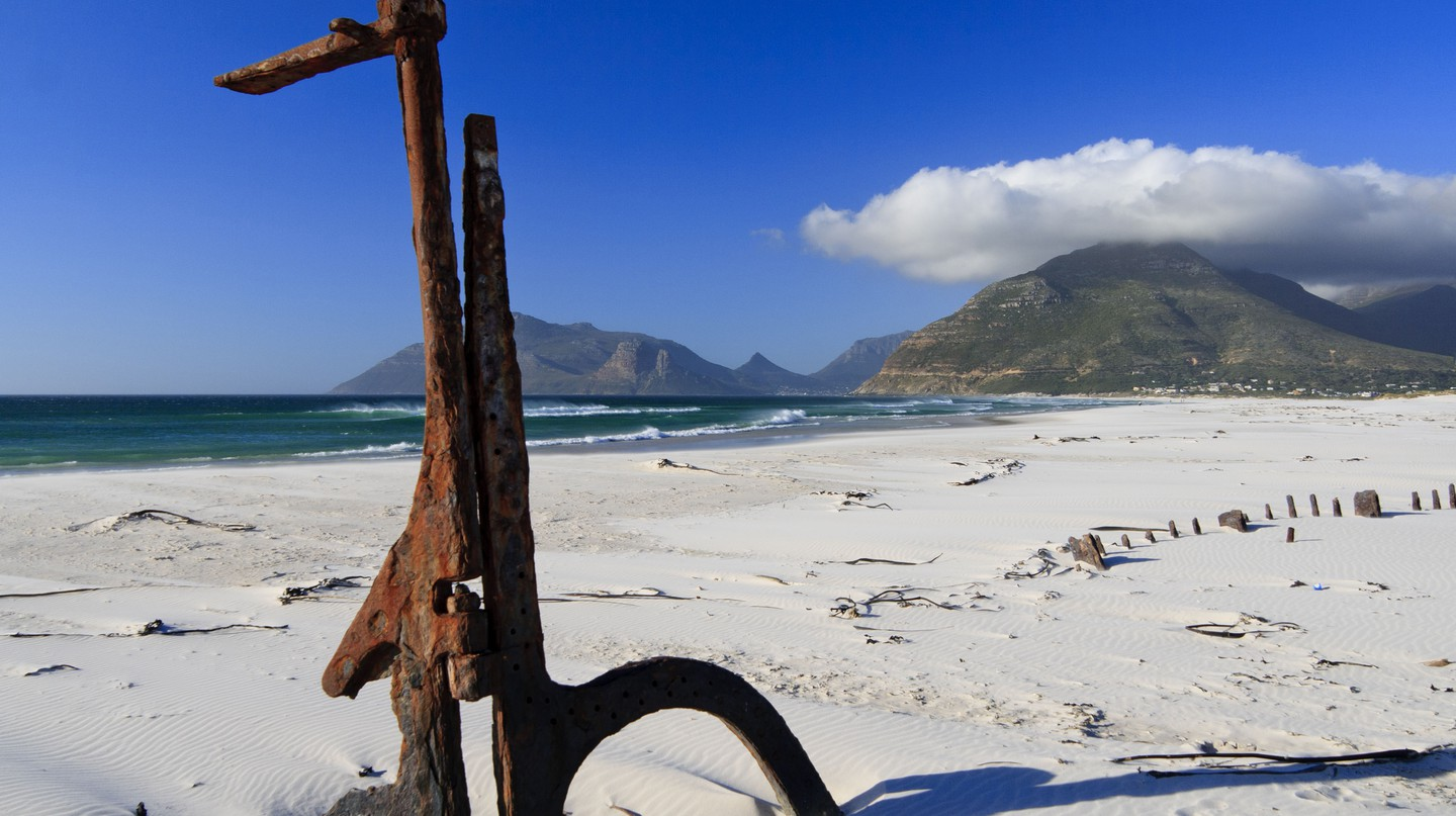 Shipwreck with rudder on the beach in Cape Town, South Africa.