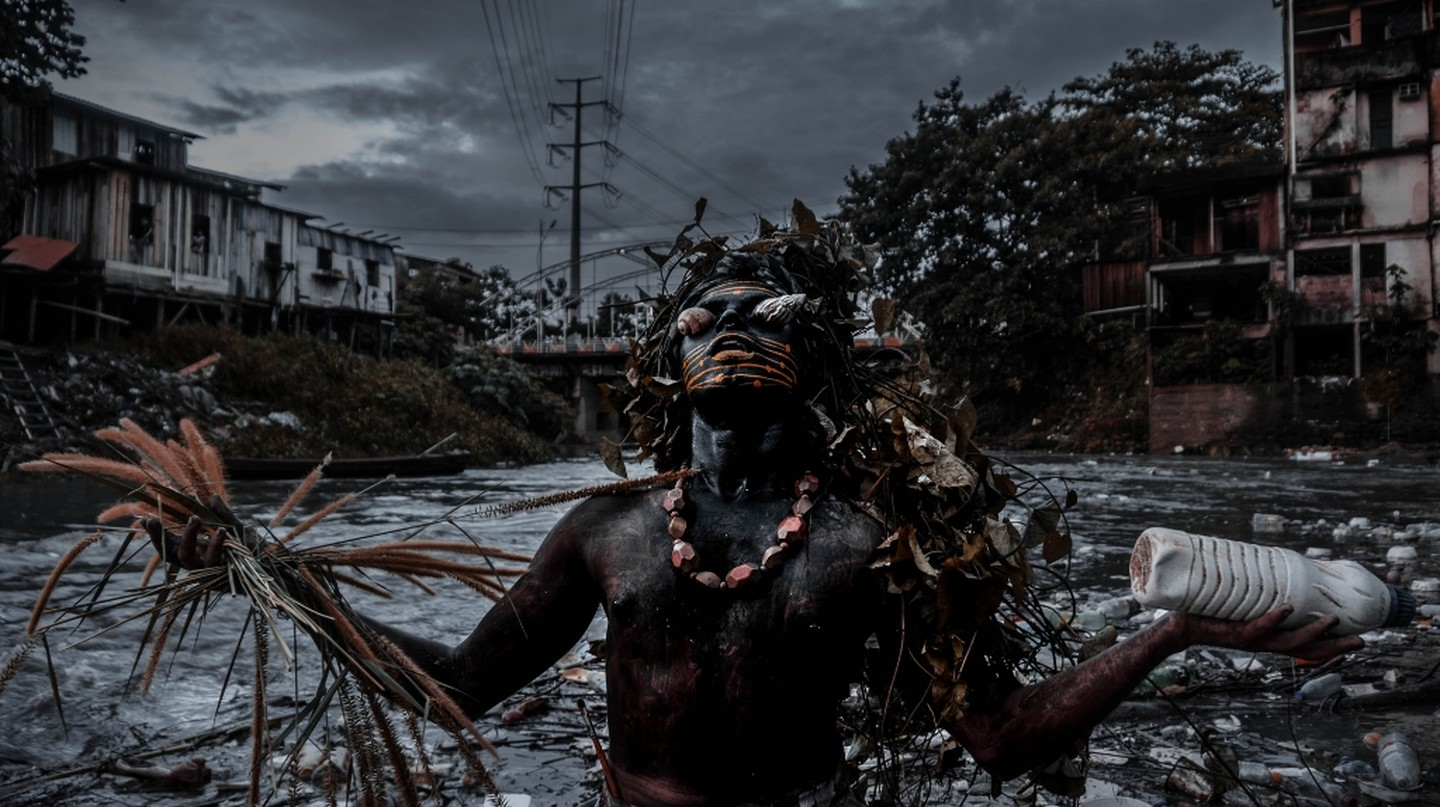 Meet Uýra, dressed in a costume made entirely of natural materials, as she stands against a backdrop of a river contaminated by plastic waste