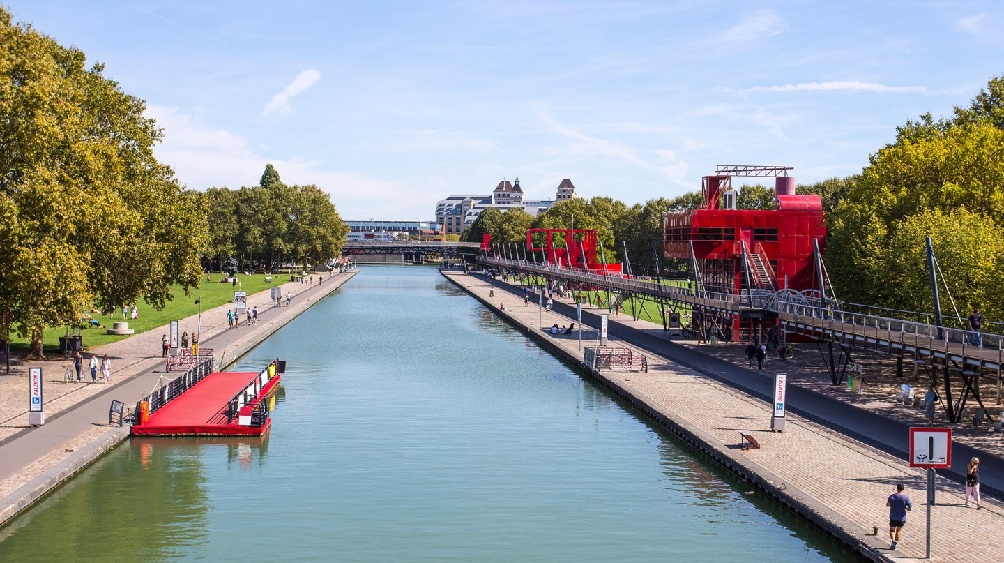 People explore the City of Science and Industry in the Parc de la Villette in Paris, France, on a sunny day